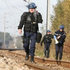 Riot police officers walk past a rail damaged by protesters at the tracks near Lieusant. (AP Photo/David Vincent/PA Images)