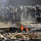 An Egyptian riot policeman throws a rock at protesters during today's clashes in the capital. (AP Photo/Khalil Hamra/PA Images)