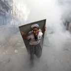 An Egyptian protester using scrap metal as a shield takes cover from tear gas during clashes with security forces. (AP Photo/Khalil Hamra/PA Images)