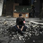 A protester sits on a mound of rocks during a temporary ceasefire with the Egyptian riot police in Cairo. (AP Photo/Tara Todras-Whitehill/PA Images)