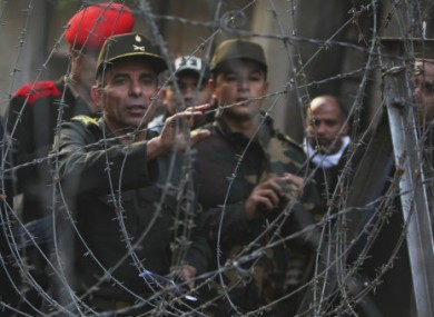 An Egyptian army officer tries to communicate with protesters across a barricade near Tahrir Sq, Cairo.
