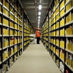 A worker in Swansea uses a barcode scanning gun to check and pick out books from a floor to ceiling racking area (Ben Birchall/PA Wire)