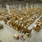A worker at the Amazon fulfilment centre in Swansea pulls a pump trolley past thousands of cardboard storage bins (Ben Birchall/PA Wire/Press Association Images)