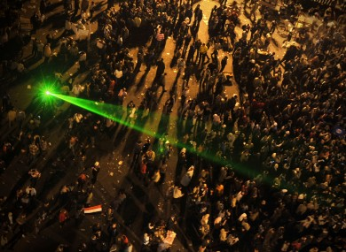 A laser lights up as thousands spend the night in Tahrir Square