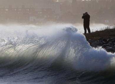 A man photographs waves at Dublin's Great South Wall today.