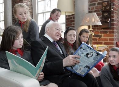 President Michael D Higgins reads a book by Oscar Wilde to schoolchildren at The Ark, Dublin.