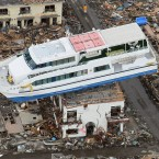 A sightseeing boat washed away by the 11 March tsunami sits on a ruined building in Otsuchi, Iwate Prefecture, Japan on 23 March. (AP Photo/Kyodo News/PA Images)