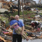 A man carries a young girl who was rescued after being trapped with her mother in their home after a tornado hit Joplin on 22 May, 2011. (AP Photo/Mike Gullett/PA Images)