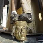This picture from 23 August shows rebel Libyan fighters trample on a statue head of Moammar Gaddafi inside his captured compound in Tripoli. The city's Green (now Martyrs) Square had been seized the previous day. Gaddafi was killed on 20 October. (AP Photo/Sergey Ponomarev)