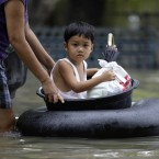 A Filipino boy rides on board an improvised float at flood-struck Calumpit town, Bulacan province, north of Manila on5 October. Flooding from back-to-back typhoons has affected more than half a million people in northern Philippines. (AP Photo/Aaron Favila/PA Images)