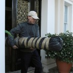 A man carries a package from the residence of the Iranian Charge D'Affaires in Knightsbridge as Iranian diplomats prepared to leave London. (Image: Dominic Lipinski/PA Wire)