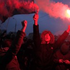 Protesters light flares during the rally (AP Photo/Sergey Ponomarev)