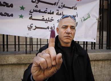 A man shows his inked finger after voting in Damascus today.