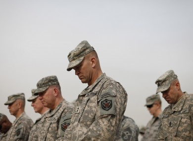 Military personnel bow their heads during ceremonies marking the end of the war in Iraq today.