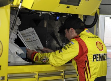 Kurt Busch reads the newspaper before practice for the NASCAR Brickyard 400 (file photo).