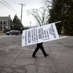 JB Webb, of Manchester, NH, carries a sign to the Webster School yesterday, where primary voting was taking place. (AP Photo/Evan Vucci/PA Images)