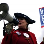 Rep Ron Paul supporter Melina Brajovic calls out to voters driving into a polling station during the first-in-the-nation presidential primary, at Hilltop Middle School in Manchester, New Hampshire. (AP Photo/Matt Rourke/PA Images)
