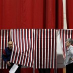 Ballot inspector Connie Bell holds open a curtain on a voting booth during voting in the NH presidential primary at Memorial High School in Manchester. (AP Photo/Matt Rourke/PA Images)