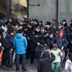 One man reacts as he pushed away by police officers while refusing to leave the Apple store in Beijing earlier. (AP Photo/Andy Wong/PA Images)