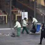 A police officer walks by workers cleaning up garbage left by those gathered outside the Apple flagship store in Beijing this morning. (AP Photo/Andy Wong/PA Images)