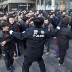 A policeman tries to drag away people who refused to leave the Apple store in Beijing today. (AP Photo/Andy Wong/PA Images)