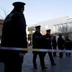 Police officers stand guard as they seal off the area near Apple's Beijing flagship store after clearing the crowds this morning. (AP Photo/Andy Wong/PA Images)