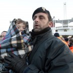 A police officer holds a baby wrapped in a blanket as passengers of the luxury ship arrive on a ferry in Porto Santo Stefano, Italy, on Saturday. (AP Photo/Gregorio Borgia/PA Images)