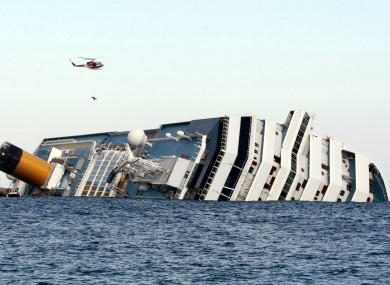 An Italian firefighter helicopter lifts up a passenger from the luxury cruise ship Costa Concordia