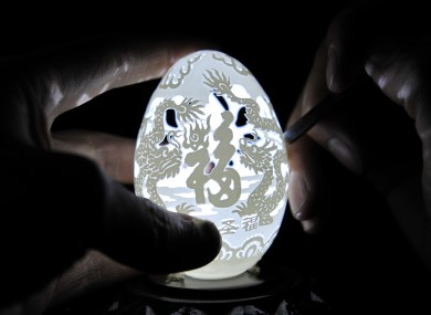 Wen Fuliang carves dragon images on an eggshell to welcome the Spring Festival on January 12, 2012 in Xi'an, Shaanxi Province of China.