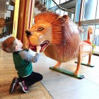 A young boy plays with a lion-shaped coffin.