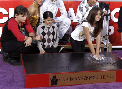 Paris Jackson presses the glove into cement as her brothers look on.