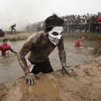 A competitor crosses one of the obstacles on the gruelling Tough Guy course. (AP Photo/Jon Super/PA Images)