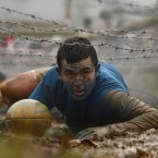 A competitor pushes a rugby ball as he crawls under barbed wire. (AP Photo/Jon Super/PA Images)