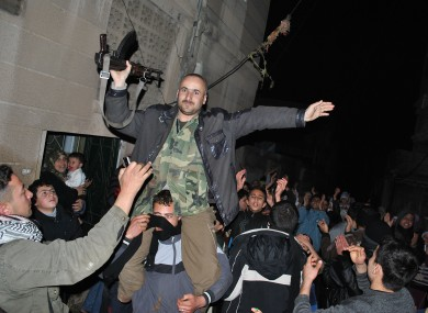 Anti-Syrian regime protestors hold up a Syrian army defector as they chant slogans during a protest in central Syria last night.