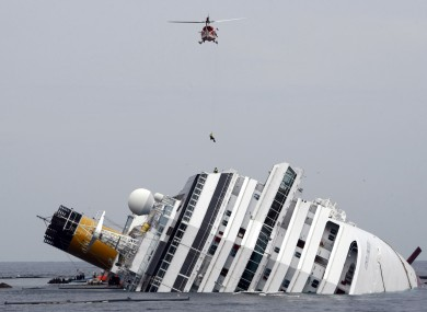 An Italian firefighter being lowered onto the Costa Concordia during the search.