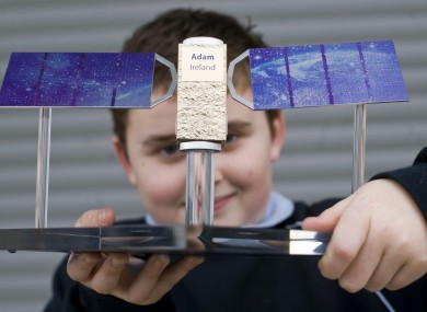 Adam Vaughan poses with a model of the Galileo satellite that will be named after him.