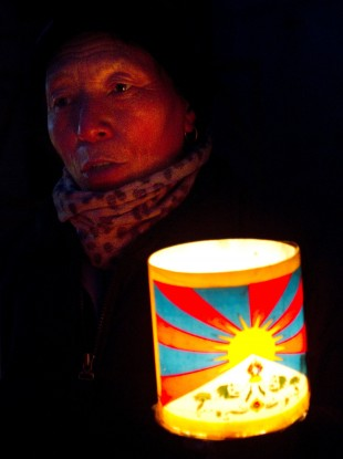 A Tibetan Buddhist man holds a lantern with the flag of Tibet during a protest in January 2012.