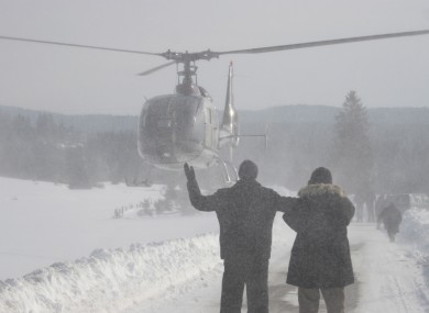 Bosnian people wave to a helicopter as they await food supplies after being cut off by the snow.