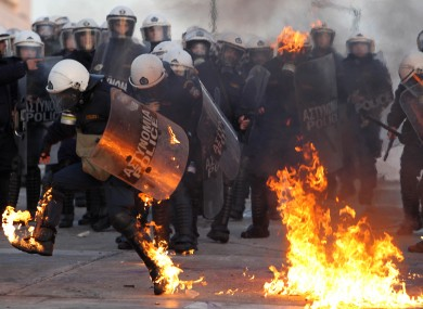 A riot police officer tries to extinguish flames from a petrol bomb thrown by protestors outside the Greek parliament.