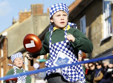 Harry Bennett, 6, from Olney Infant Academy in England races to the finish line of today's pancake race.