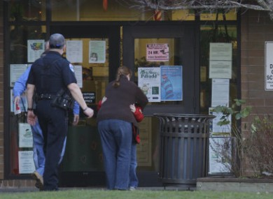 A child hugs an adult near the entrance to the school in Bremerton after yesterday's shooting.