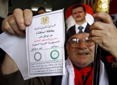 A Syrian man holds up his ballot paper at a polling station during a referendum on the new constitution in Damascus yesterday. The EU's foreign ministers today introduced new asset embargoes against Syria.