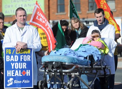Paddy McKitterick (L) and Niall O'Leary (R) push Niamh Quigley, 9, in a hospital bed at a protest to save emergency services at St Columcille's Hospital.
