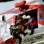 Rescue workers carry an elderly woman who had evacuated to the rooftop of an elementary school onto a Sapporo City fire department helicopter in Sendai, Miyagi Prefecture on 12 March 2011. (Kyodo/PA Images)