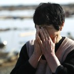 A resident wipes tears as she finds no remains of her home in Soma city, Fukushima prefecture three days after disaster struck in March 2011. (AP Photo/Wally Santana/PA Images)