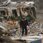A man searches for a family member in the ruins of tsunami-hit area in Onagawa, Miyagi Prefecture a week after the earthquake. (AP Photo/Shuji Kajiyama/PA Images)