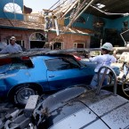 Construction workers lift a piece of sheet metal off of classic cars in a storm-damaged display room at Branson Auto World in Branson, Missouri. (AP Photo/Mark Schiefelbein/PA Images)
