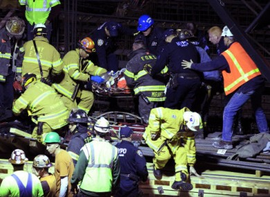 Emergency services remove an injured man from the scene of a crane collapse in Manhattan.