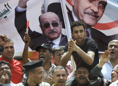 Supporters of former Egyptian Vice President Omar Suleiman chant in front of his posters