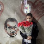 An Egyptian flowers vendor in front of graffiti depicting president Hosni Mubarak, two days before Mubarak is to hear the verdict on charges of corruption and complicity in killing protesters during last year's uprising. (AP Photo/Amr Nabil)